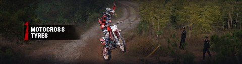 un competidor de motocross en mitad de un salto saludando al público